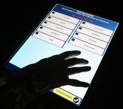 A Hand Touches The Screen Of A Voting Machine
