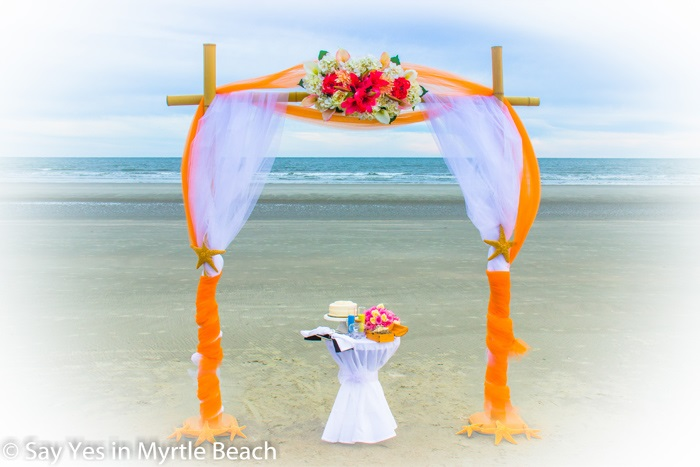 Orange and white tulle wrapped arbor