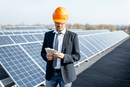 Man with safety helmet holding money on the roof with solar panels