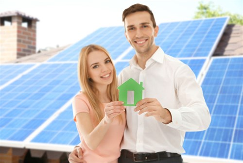 Happy couple holding figure of house and solar panels on background